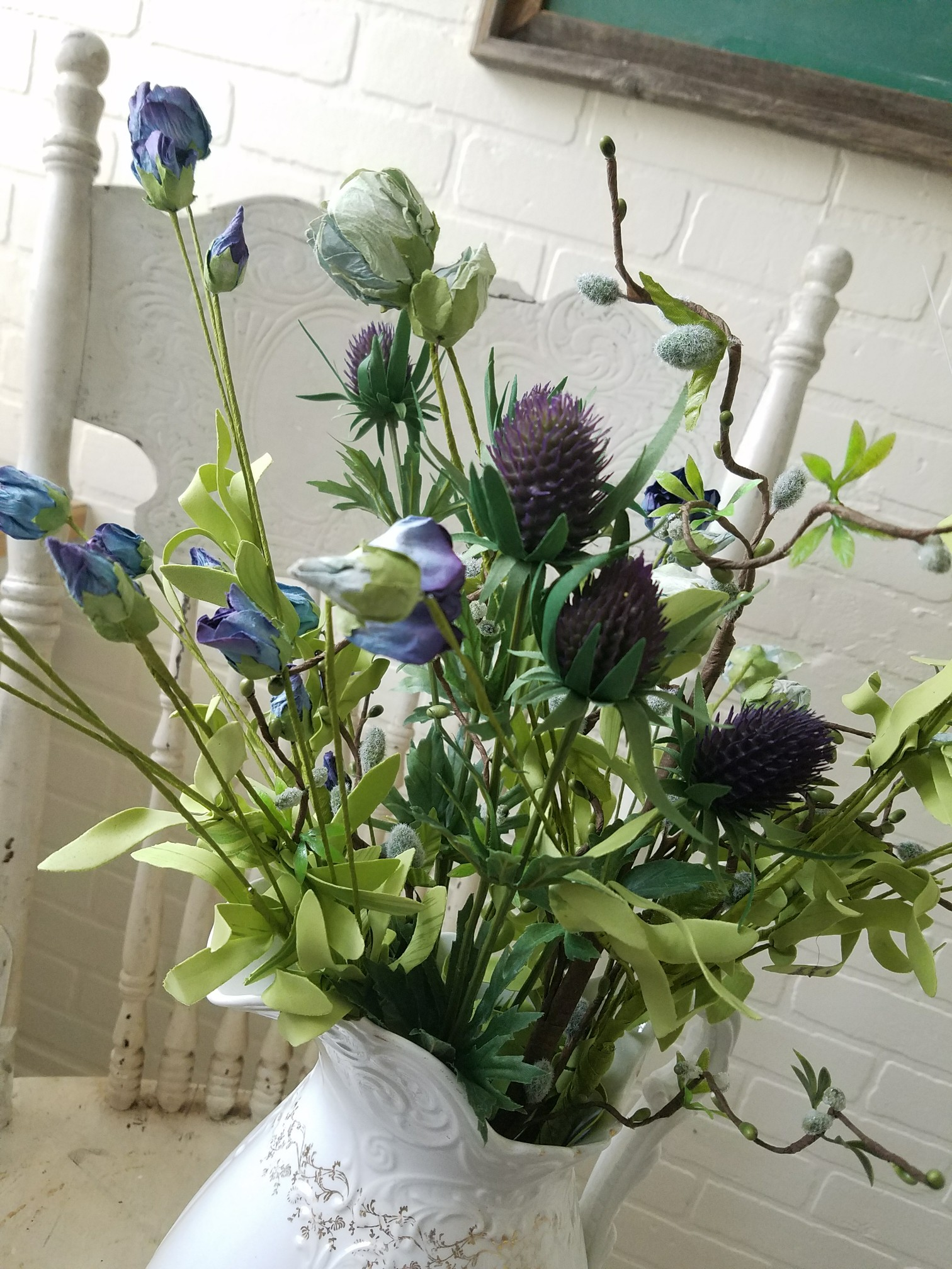 Amazing colors in this spring bouquet thistle, blue roses, pussy willow in ironstone