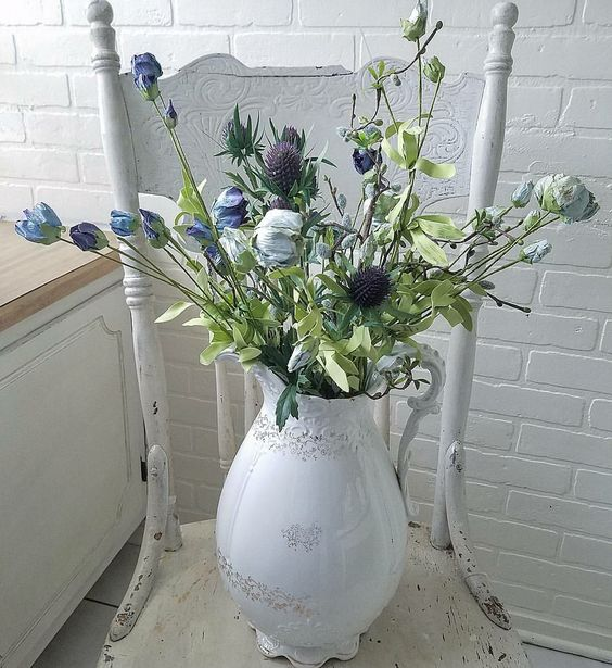 Gorgeous shabby chic spring bouquet in an old ironstone pitcher with blue roses, thistle, and pussy willow displayed in an antique white chippy chair