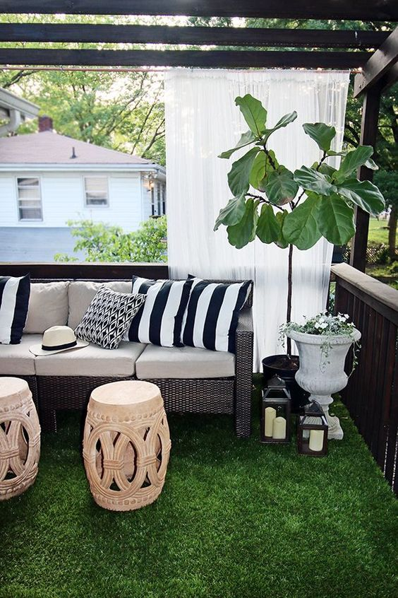 Beautiful outdoor space with faux grassurns fiddle leaf fig