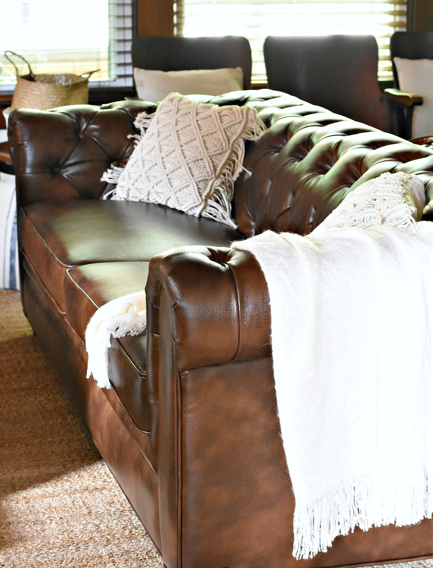 brown leather Chesterfield with boho chic macrame pillows and jute area rug jute rug ideas