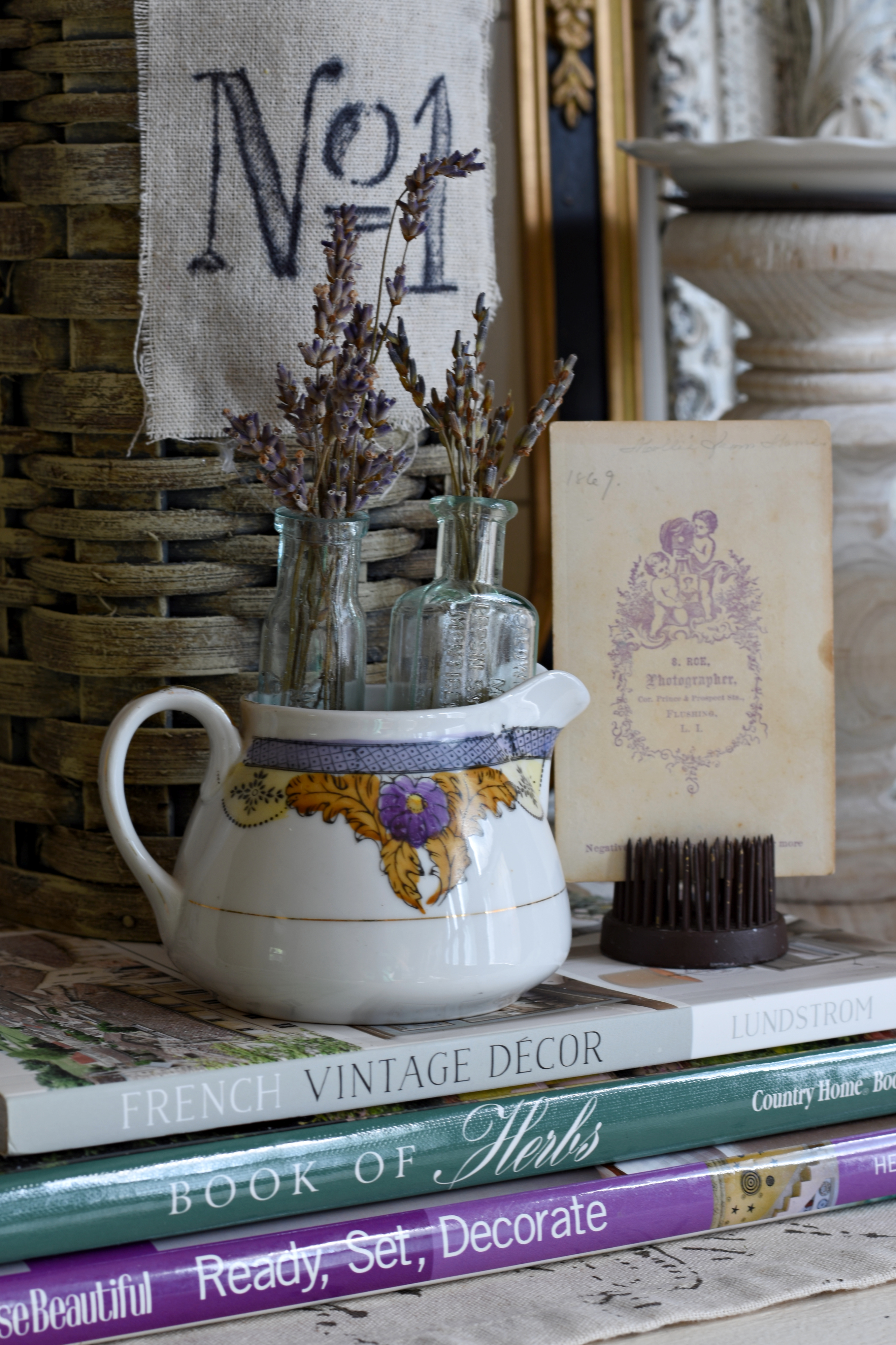 pretty vintage vignette with purple accents purple transfeware, vintage ephemera, lavender in vintage teal glass bottles, vintage flower frog, decorating books, french basket, antique picture frames