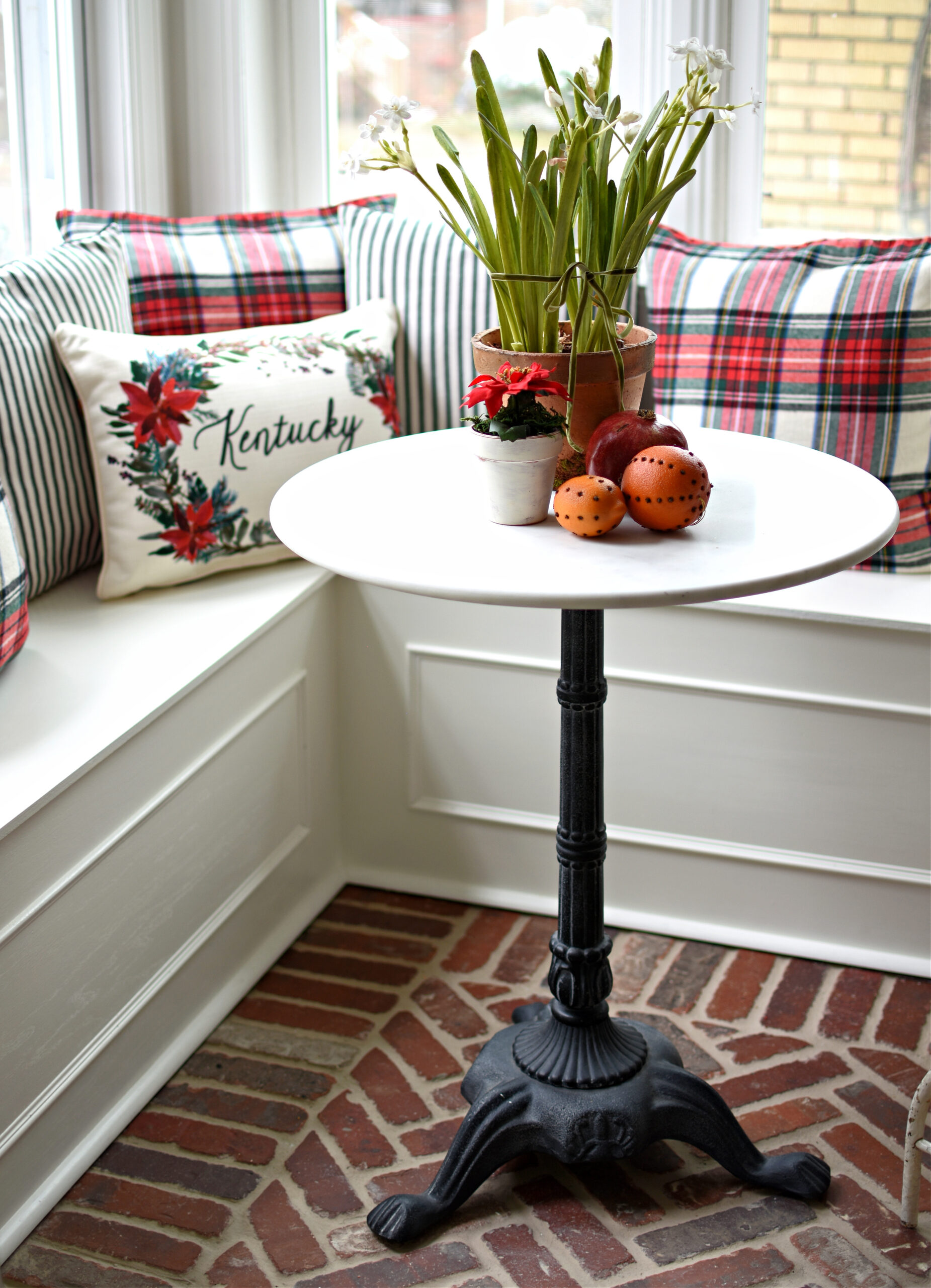 Cute Christmas breakfast nook ideas plaid pillows ticking stripe pillows on a window seat. World Market Marble Bistro Table and herringbone brick floors. Christmas kitchen