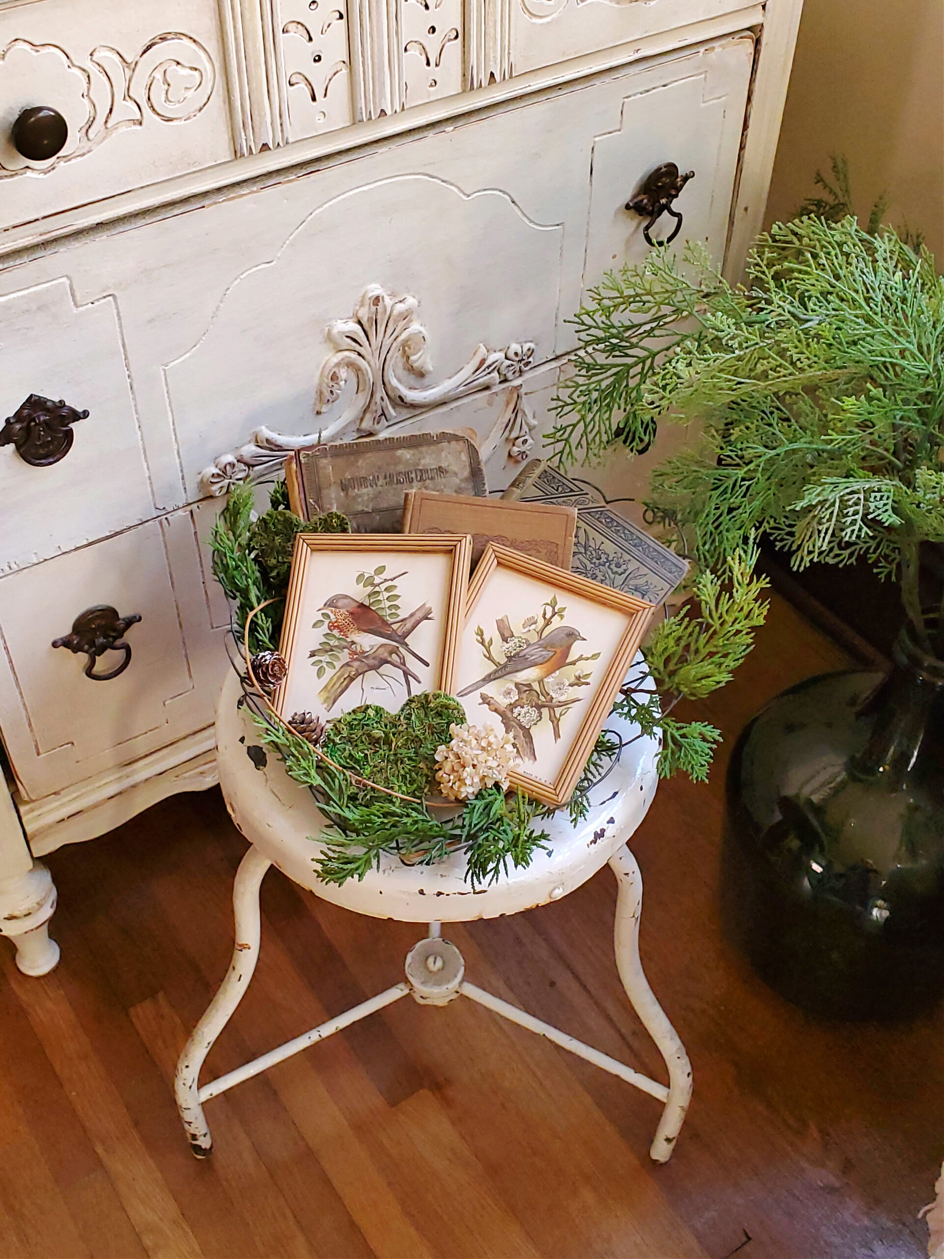 Vintage bird pictures and vintage books in a wire heart basket with evergreens nature inspired February decor